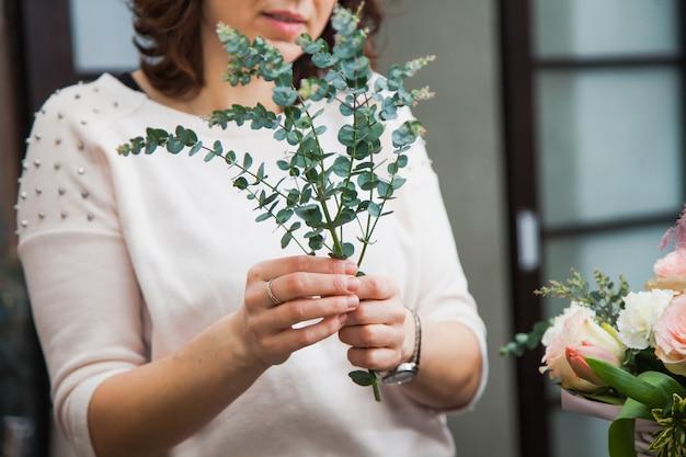 白いバスケットに花束を作るために花を集める女性の花屋のデザイナー。休日や装飾のためのプレゼントを準備する花屋。花の配達の概念。
