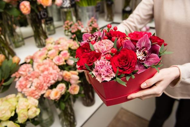 Female florist hands arranging floral composition