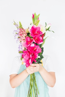 Female florist hiding her face behind bunch of flowers