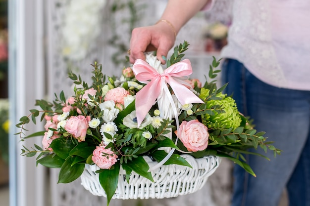 Female florist holding a beautiful bouquet of roses in white basket