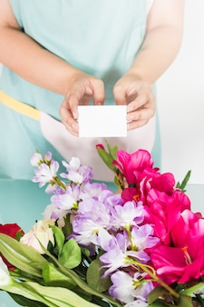 Female florist holding blank visiting card over bunch of fresh flowers