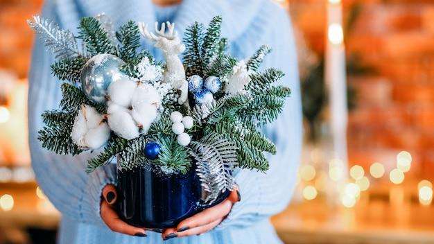 크리스마스 배열, 전나무 나무 잔 가지와 냄비를 들고 여성 꽃집. 공간을 복사하십시오.