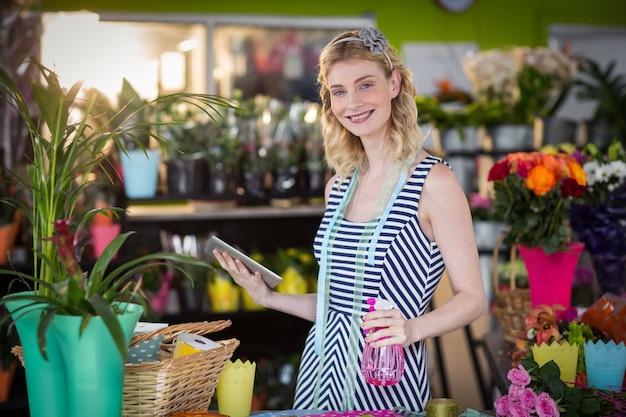 Female florist holding digital tablet and spray bottle