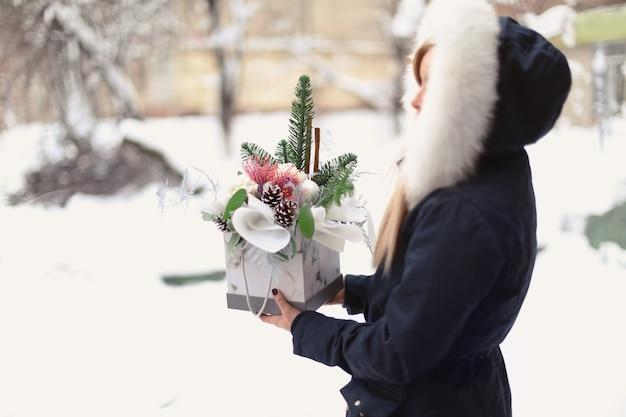 屋外の箱に花の組成物を保持している女性の花屋
