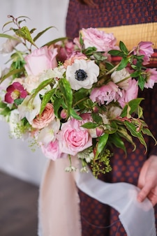 Female florist holding a freshly made blooming floral bouquet of pastel against a gray wall.