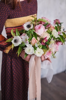 Female florist holding freshly made blooming floral bouquet