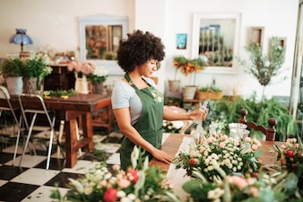 Female florist holding glass bottle in shop
