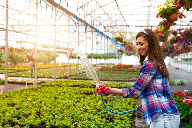 호스를 들고 온실에서 식물을 급수하는 여성 플로리스트.