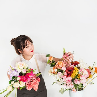 Female florist looking at flowers on white background