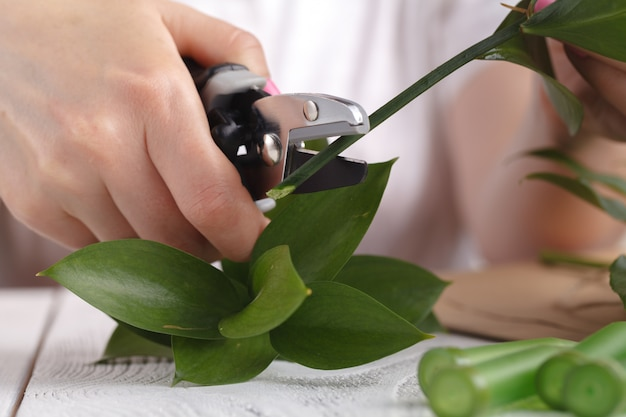 Female florist make bouqet on table working prosess