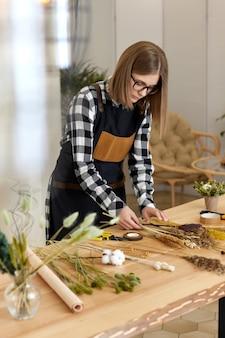 여성 꽃집은 나무 테이블에 말린 꽃과 공예 종이의 아름다운 꽃다발을 만듭니다