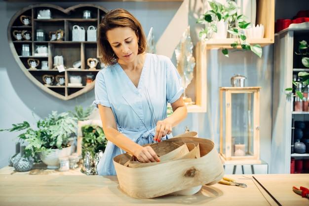 Флорист женского пола составляет цветочную композицию в магазине. украшение упаковки для букета. профессия художника-флориста