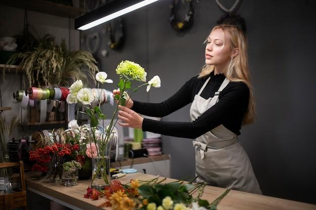 Женский флорист делает красивую композицию из цветов