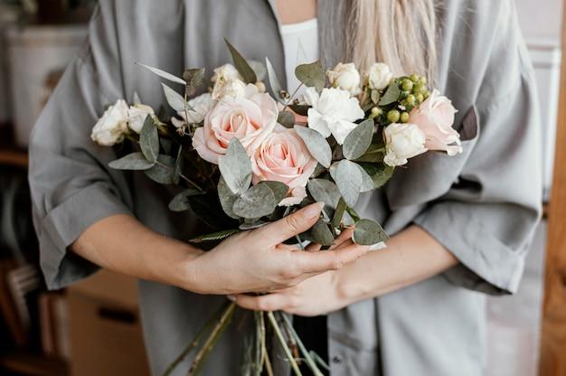 Женский флорист делает красивую цветочную композицию
