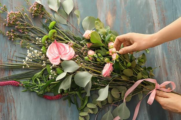 テーブルの上の美しい花の花束を準備する女性の花屋