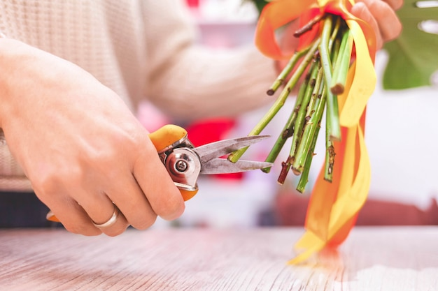 Female florist pruning rose stem at table with secateurs