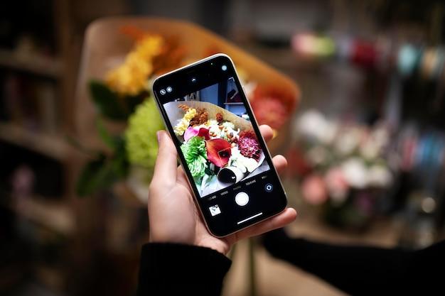 Fiorista femminile che scatta una foto di un bouquet appena fatto