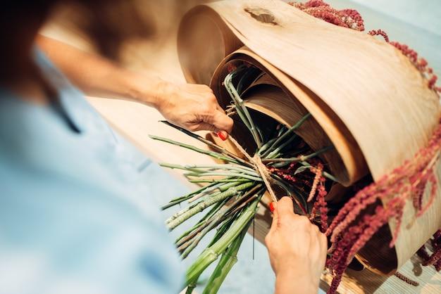 女性の花屋は店のクローズアップで花の花束を結び付けます。職場で作曲を行う花のアーティスト