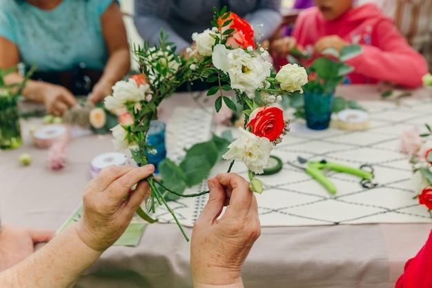 Флорист женского пола, несосредоточенно в цветочном магазине. студия цветочного дизайна, изготовление декораций и композиций.