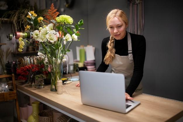 Fiorista donna che utilizza un computer portatile al lavoro