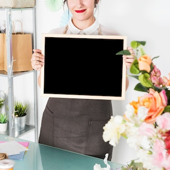 Female florist with blank slate in floral shop