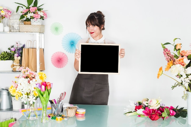 Female florist with blank slate looking at camera