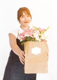 Fiorista femminile con il sacchetto di carta del fiore su fondo bianco