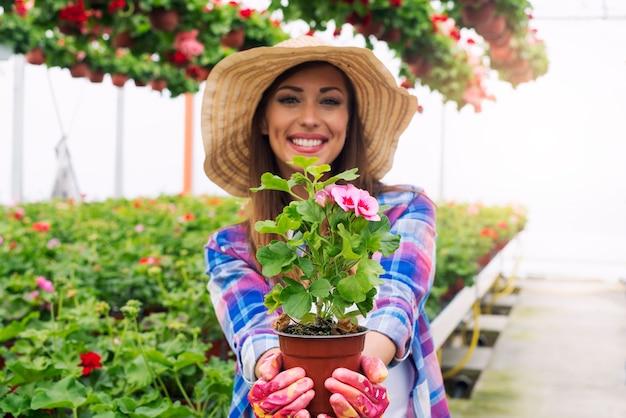 温室ガーデンセンターで花の植物を保持している歯を見せる笑顔を持つ女性の花屋。