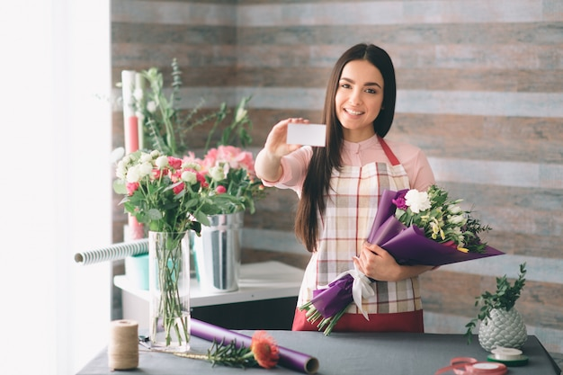 Female florist at work: pretty young dark-haired woman making fashion modern bouquet of different flowers. women working with flowers in workshop. she is holding a business card.