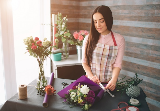 Female florist at work: pretty young dark-haired woman making fashion modern bouquet of different flowers. women working with flowers in workshop