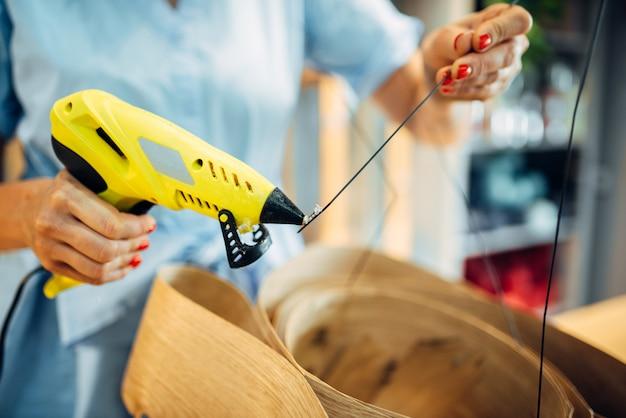 Цветочница работает с клеевым пистолетом в цветочном магазине. украшение упаковки для букета. профессия художника-флориста