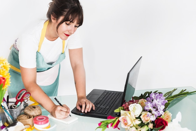 Female florist writing notes on notepad with laptop on desk