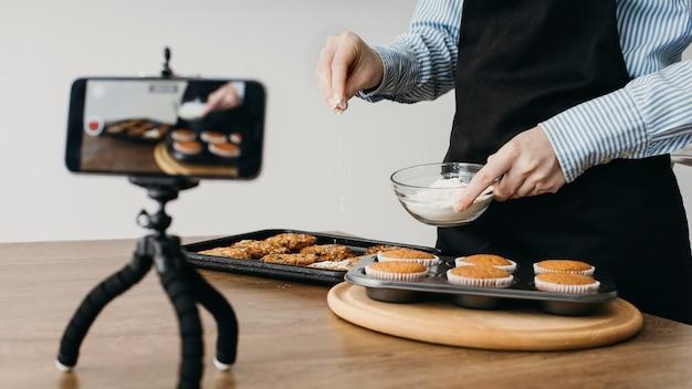 요리하는 동안 스마트 폰으로 집에서 스트리밍하는 여성 음식 블로거