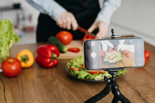 Female food blogger streaming at home while cooking