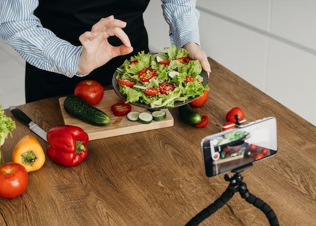 Blogger di cibo femminile in streaming durante la cottura a casa
