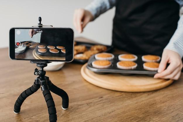 Женский кулинарный блогер смотрит на смартфон дома во время готовки