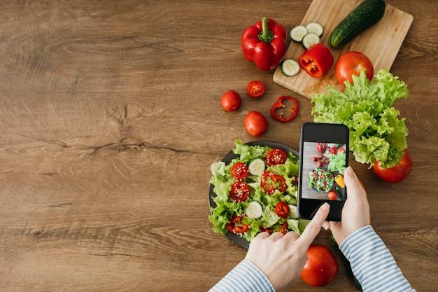 Blogger alimentare femminile in streaming con lo smartphone a casa