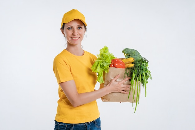 Female food delivery worker with a bag of vegetables