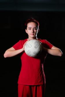 Женский футболист держит мяч