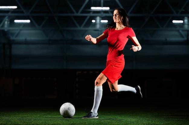 Giocatore di football americano che dà dei calci alla sfera