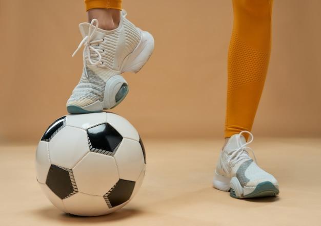ボールに足を置く女性のサッカー選手