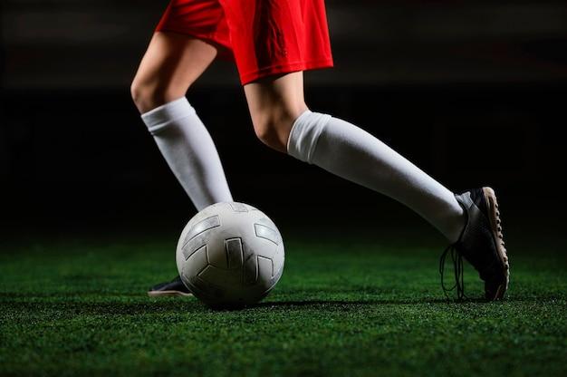 Женский футболист работает рядом с мячом