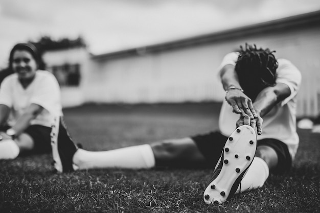 Female football player stretching before a match
