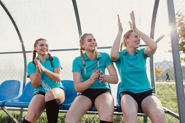 Female football players sitting on a bench and clapping