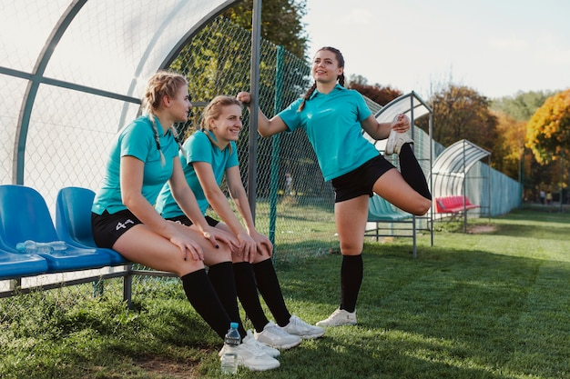 Female football players sitting on a bench