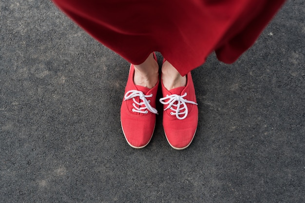 Female foots in red sneakers on the pavement. view from above
