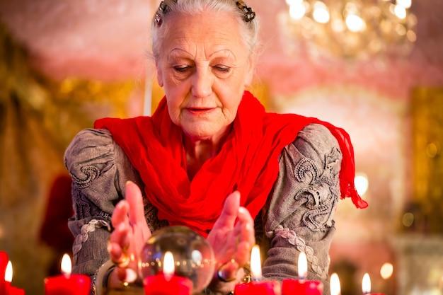 여성 점쟁이 또는 난해한 오라클, seance 동안 수정 구슬을 들여다보고 해석하고 질문에 답함으로써 미래를 봅니다.