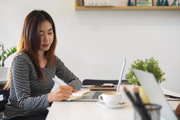 여성 프리랜서는 커피숍에서 휴대용 노트북을 사용하여 집중적으로 작업하고 메모를 합니다.