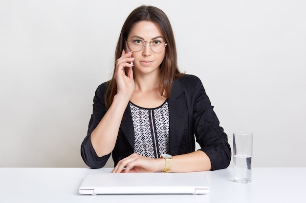 Female freelancer enjoys distant work at home, has telephone conversation, sits at white desk near laptop computer and glass of water, isolated on white. people and technology concept