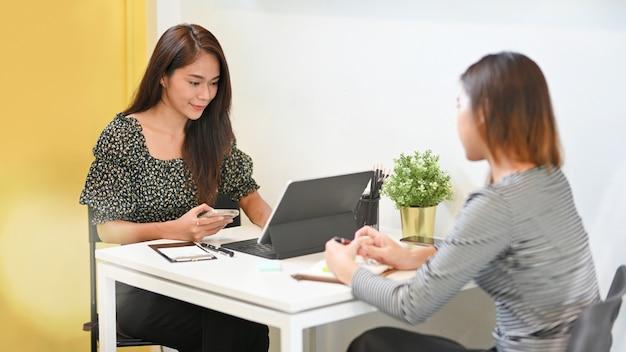 커피숍 직업에서 비즈니스 인사와 업무 인터뷰를 하는 여성 프리랜서
